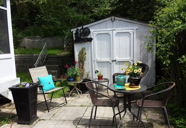 Backyard with Home Depot Canada patio, tables and planters