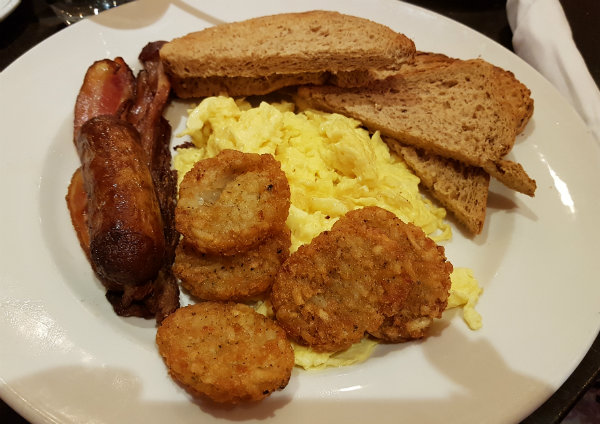 Sunrise Breakfast with scrambled eggs, bacon, sausage and potato pancakes at Green Eggplant Mediterranean Grill