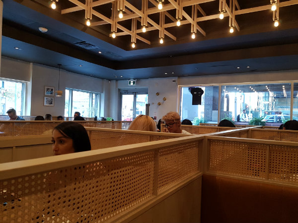 Diners are seated in a grid at KaKa All You Can Eat Sushi Restaurant