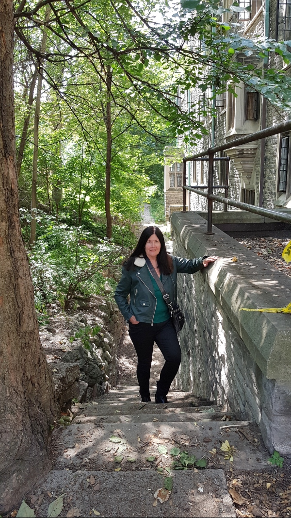 Me on a set of stairs behind Victoria College at the University of Toronto St. George Campus.